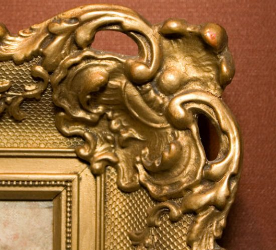 decorative gold picture frame on brown wall