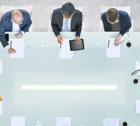 business men sitting around board room table having a meeting
