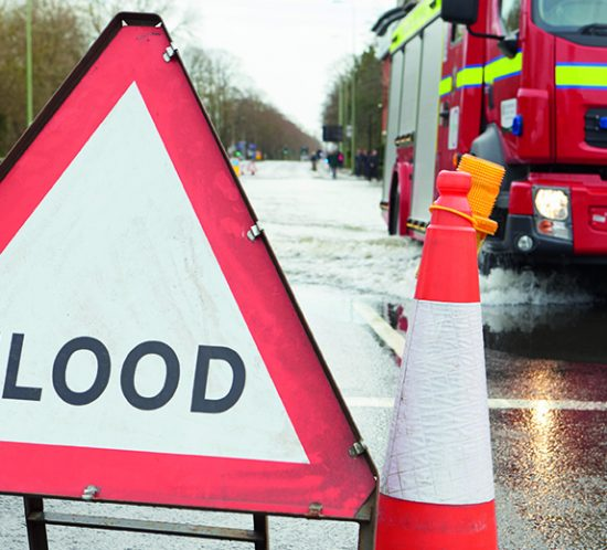 flood warning sign and traffic cone in road